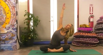 Female Yoga master sitting legs crossed stretching left arm in the air.