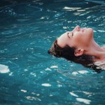 Woman relaxing by floating on her back in pool