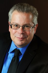 Robert Greenberg Headshot: Graying Hair, wearing glasses, a slight smirk, black suit and tie with teal colored shirt