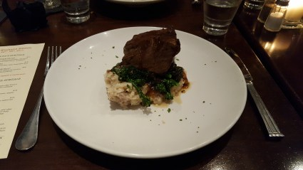 Braised Short Rib with smashed potatoes, seasonal vegetables, and a red wine demi glace.