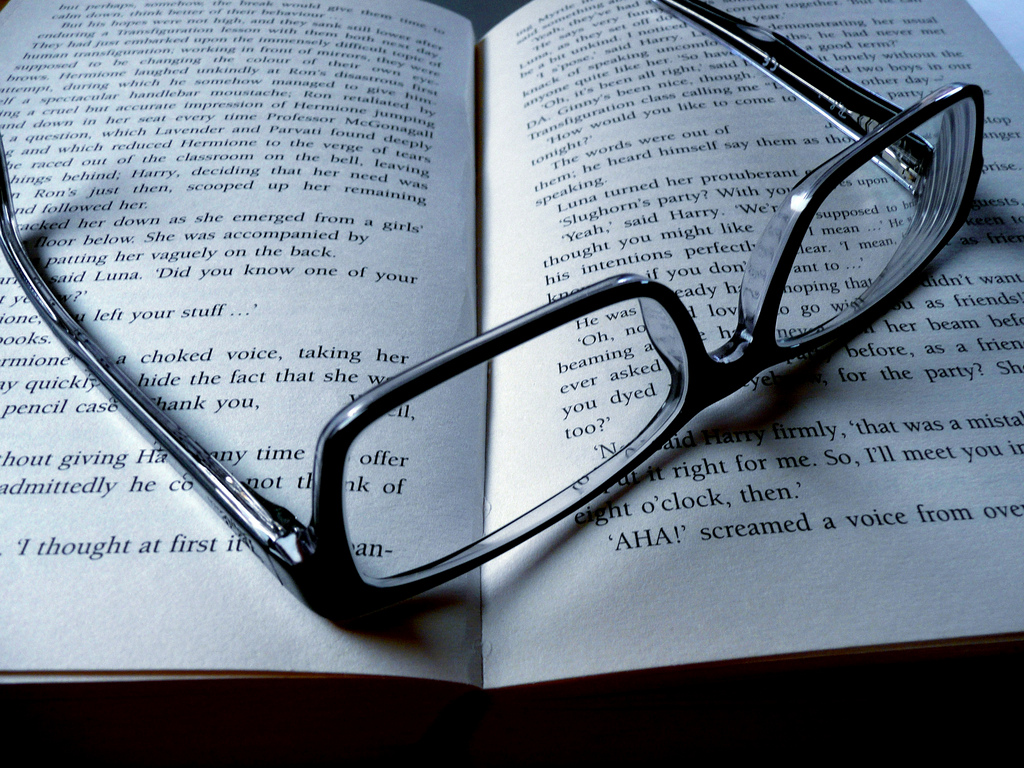 oblique view of a book on which someone has laid their black rimmed glasses
