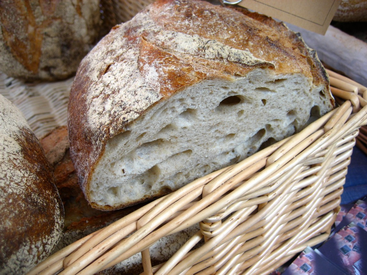 Loaf of bread with slice missing in a wicker basket