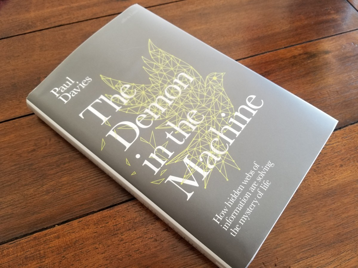 Photo of the book The Demon in the Machine by Paul Davies sitting on a wooden table. The cover is primarily the title in a large font superimposed on a wireframe of a bird in which the wireframe is meant to look like nodes in a newtowrk