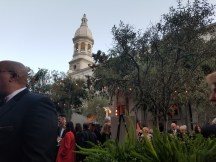 People mingling in a garden-like setting with the church in the background