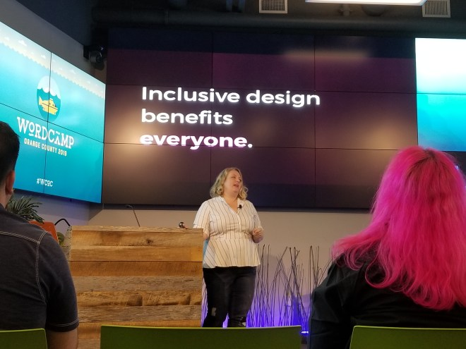 "Natalie standing next to the podium with a slide from her presentation on the screen behind her that reads ""Inclusive design benefits everyone."""