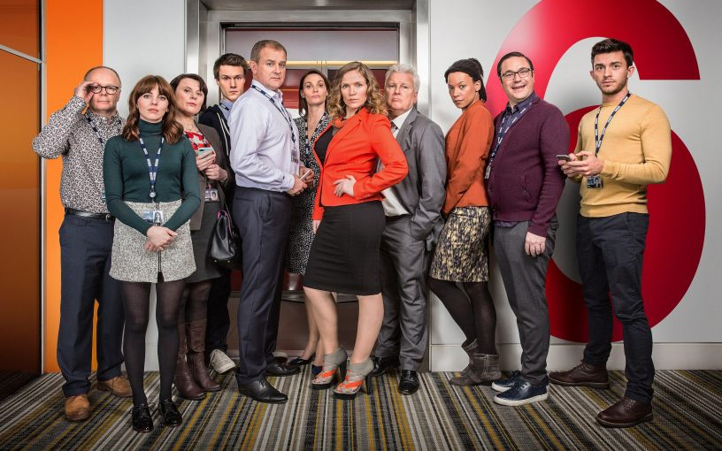 The majority of the cast of the BBC series W1A poses for a promo photo on set