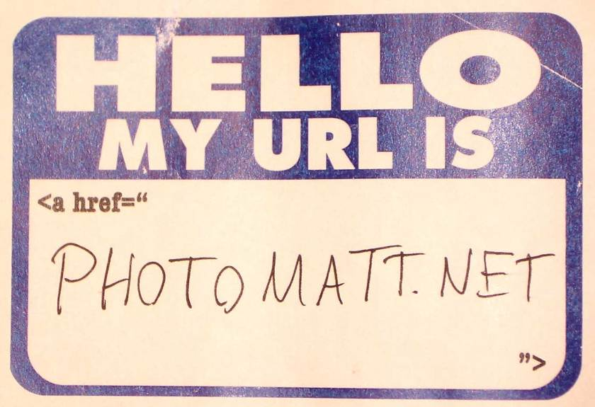 "A common sticker-type name tag that is preprinted with the large text ""Hello My URL is"" with smaller text underneath that reads <a href=""  ""> and a blank space in the middle where someone has handwritten in pen ""photomatt.net"""
