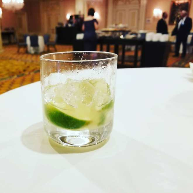 Cadillac margarita with lime wedge sitting on a table