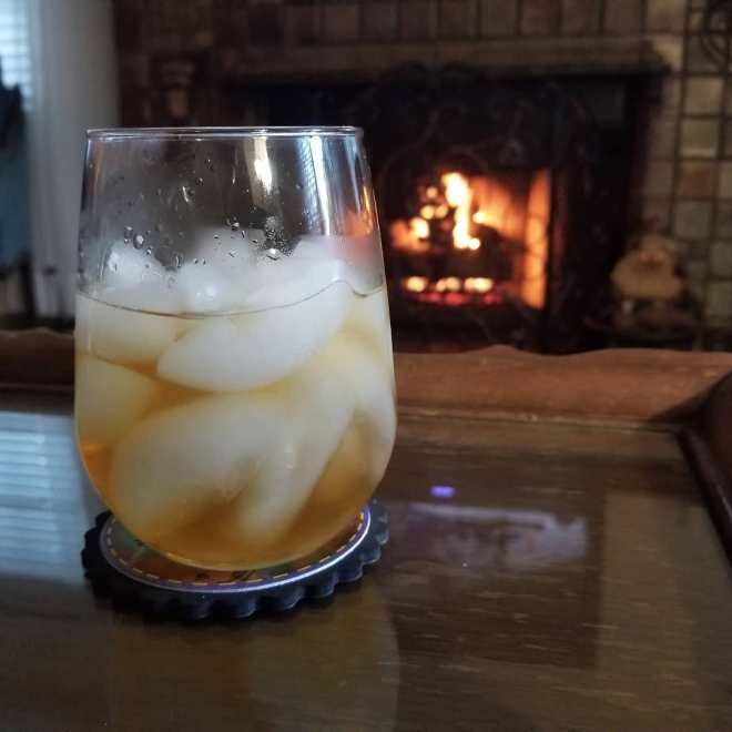 A cocktail on a table with a fire burning in the fireplace in the background