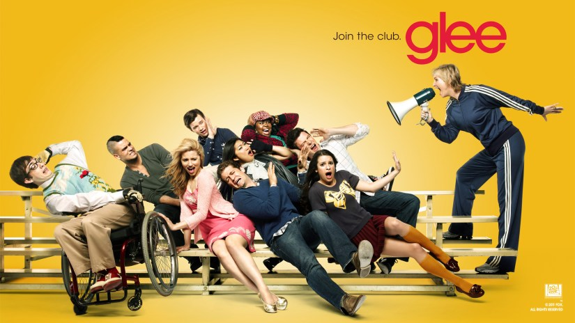 Poster of Sue with a bullhorn yelling at the rest of the Glee cast who are sitting on bleachers