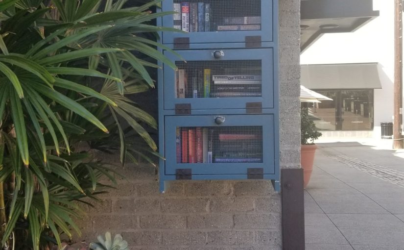 Hugus Alley's blue Little Free Library with three sections