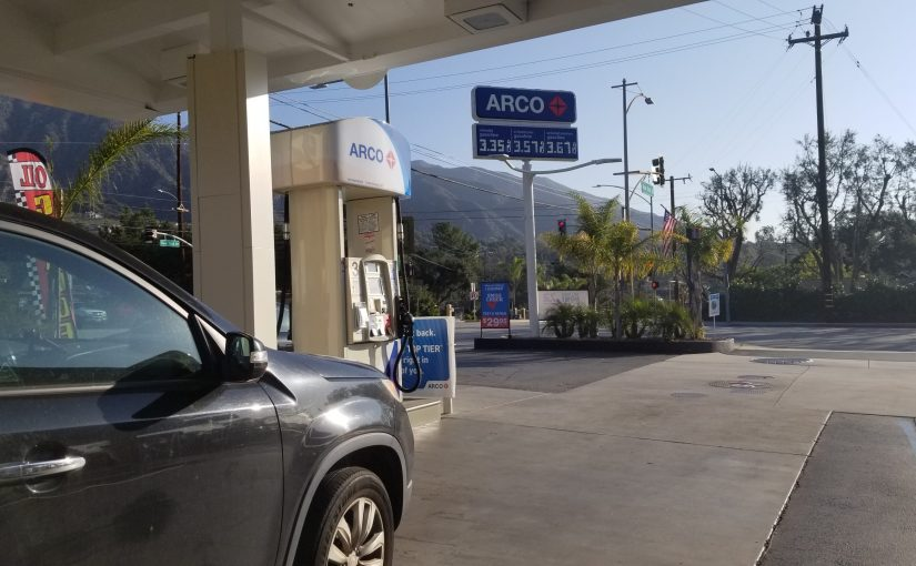Black SUV at an Arco gas station with a blue sign in front of the mountains