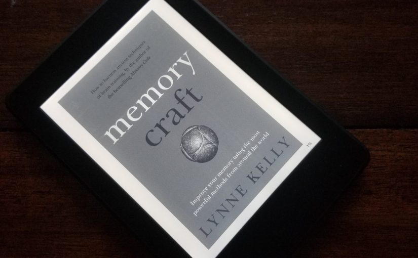 Cover of Memory Craft by Lynne Kelly on a Kindle Paperwhite sitting on a wooden table