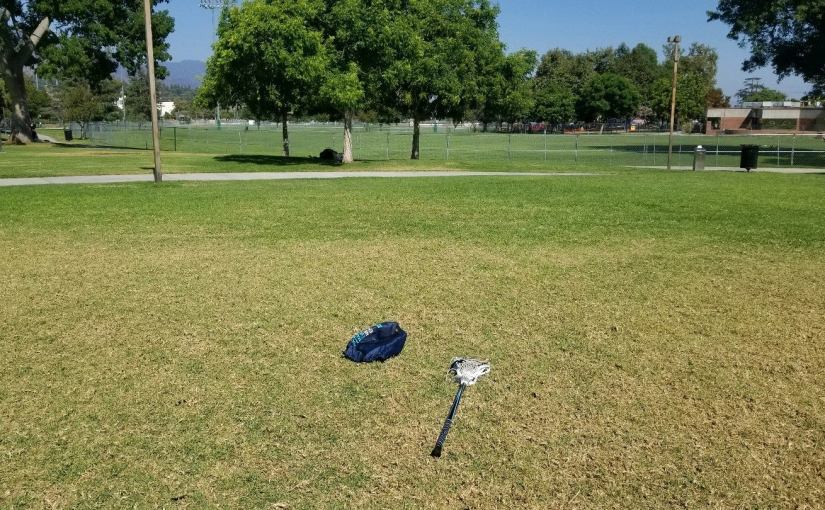 Dry, but still green grass with a lacross stick in the foreground
