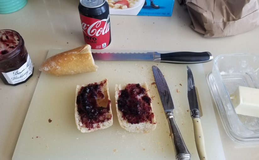 French bread cut in half with butter and blackberry jam