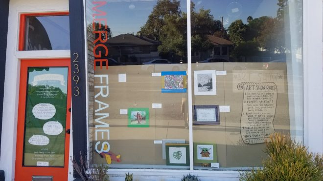 Art display in the closed storefront of Merge Frames