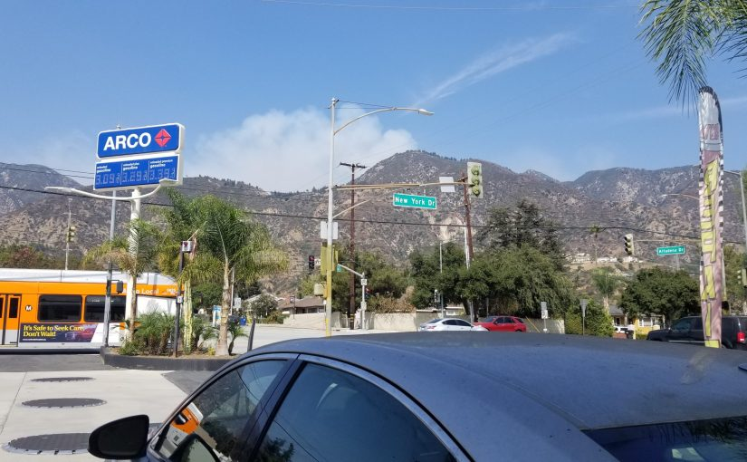 Exterior of the gas station looking up at the mountains with blue sky and smoke coming off the mountain from the Bobcat fires