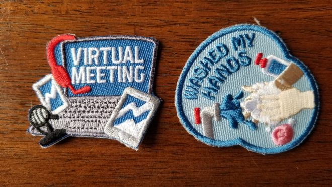 Two iron on badges; one is a computer emblazoned with the words Virtual Meeting, and the second of a faucet and hands washing with soap emblazoned with Washed My Hands.