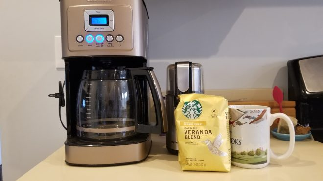 Coffee maker, grinder, cup, and a gold bag of Starbucks Veranda blend