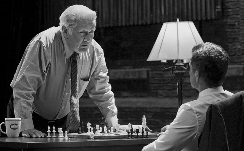 Martin Sheen stands over a chess board while talking to Rob Lowe