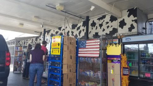 The checkout area featuring an antique US flag and a cow splotched rear wall