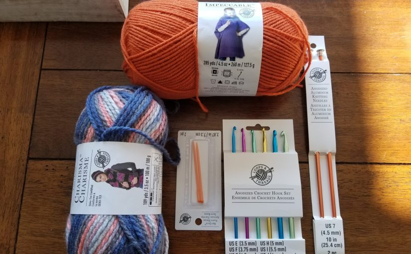 two balls of yarn and chrochet and knitting needles with receipt on wooden table