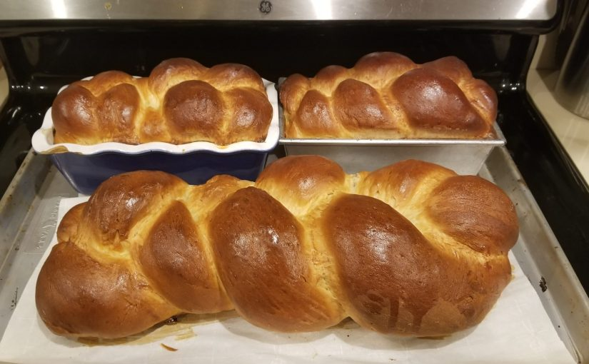 one giant plaited loaf of challah next to two smaller plaited loafs in loaf pans just coming out of the oven