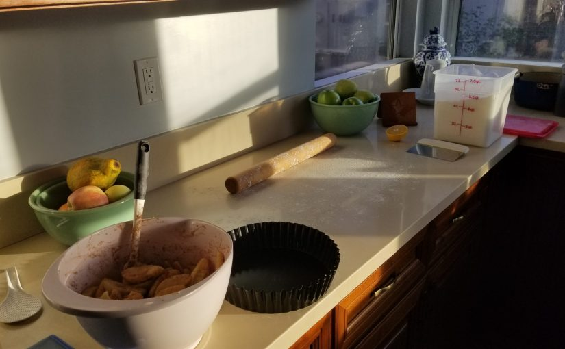 prep for apple pies with a pink bowl of sliced apples, a pie tin, rolling pin and clean space to roll out dough on the counter