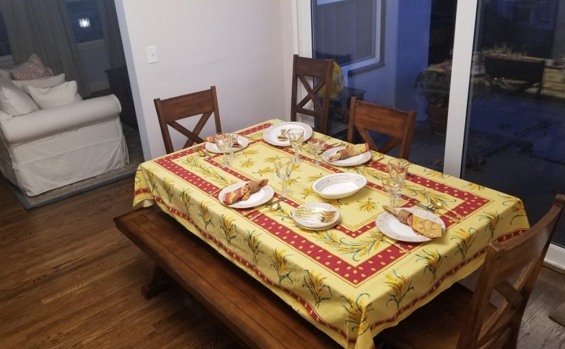 angled view of dining room table set simply for Thanksgiving with a yellow and red French country table cloth