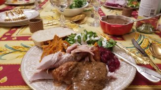 view of my Thanksgiving plate with the rest of the table in the background
