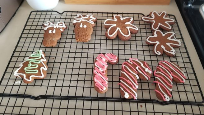 gingerbread cookies decorated in white and red royal icing cool on a wire rack