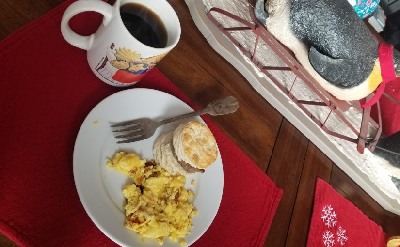 angle on dining room table with a plate of scrambled eggs, a sausage biscuit, and a cup of coffee. The penguin sled centerpiece is seen at the top of the photo.