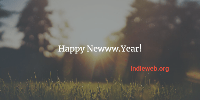 "dreamy view of grass and a forest through which the sun is rising superimposed with the text ""Happy Newww.Year! indieweb.org"""