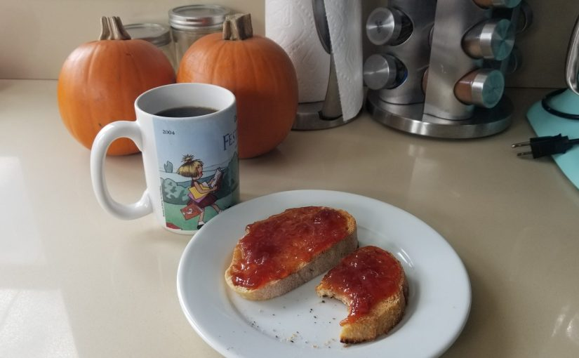 plate with two slices of toast and jam, mug of coffee, small pumpkins and various kitchen items on the counter in the background