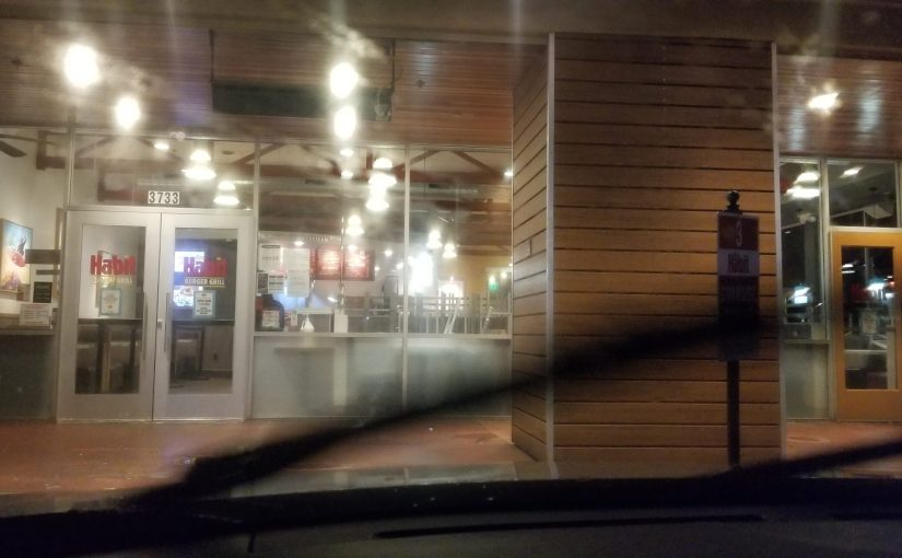 view of front of The Habit through rain soaked windshield with wipers running