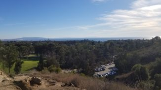 View down onto parking lot at Will Rogers State Park with trees in the midground and a generally clear, but hazy view out to the ocean and down the coastline