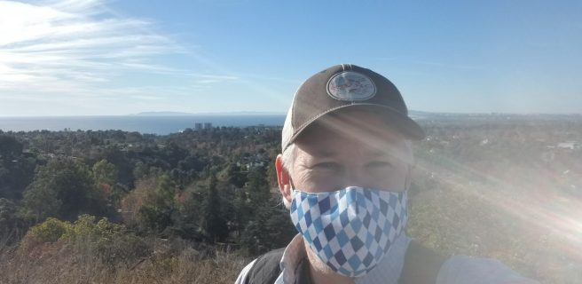 Selfie wearing a blue patterned coronavirus mask with ocean view in background and some significant sun flare in the photo