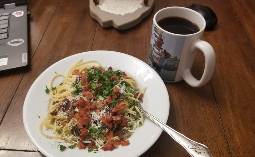 bacon and parsley on spaghetti on a plate at the dining room table next to a mug of coffee