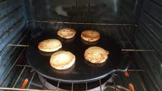 five Welsh cakes on a pizza stone in the oven