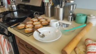 angle of Welsh cakes on a cooling rack with a bowl of sugar
