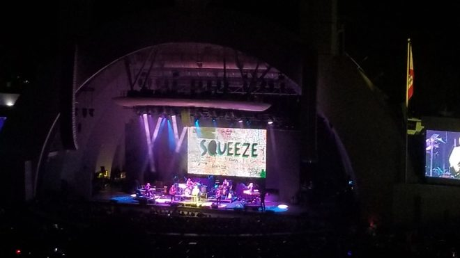 Purple lights illuminate the bandshell with the band name Squeeze projected behind the band