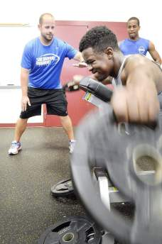 Sherwood High School football coach Chris Grier (left) works with senior Paris Atwater in the Paint Branch High School weight room recently. Dan Gross/The Gazette