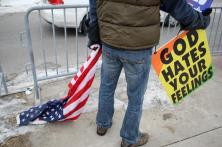 Isaiah Phelps drags an American flag as he protests on Saturday, Feb. 17 at the intersection of Stadium Boulevard and Providence Road in Columbia, Mo. Phelps is a member of the Westboro Baptist Church. The church was opposing the university's support of Michael Sam. MIKE KREBS/The Maneater