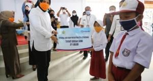Wali Kota Kotamobagu saat menyerahkan bantuan anak asuh kepada salah satu siswa.