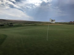 On 4th green with wind straining the flagstick.