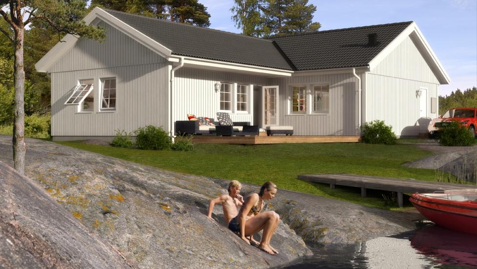 Bild av baksidan av ett Älvsbyhus Ymer med altan byggd i vinkeln på huset. Huset med sin stående träpanel är målat vitt och placerat precis vid vattnet på en sjötomt med klippor.