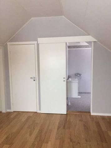 Bild inifrån sovrummet. Två fönster i ryggen.
