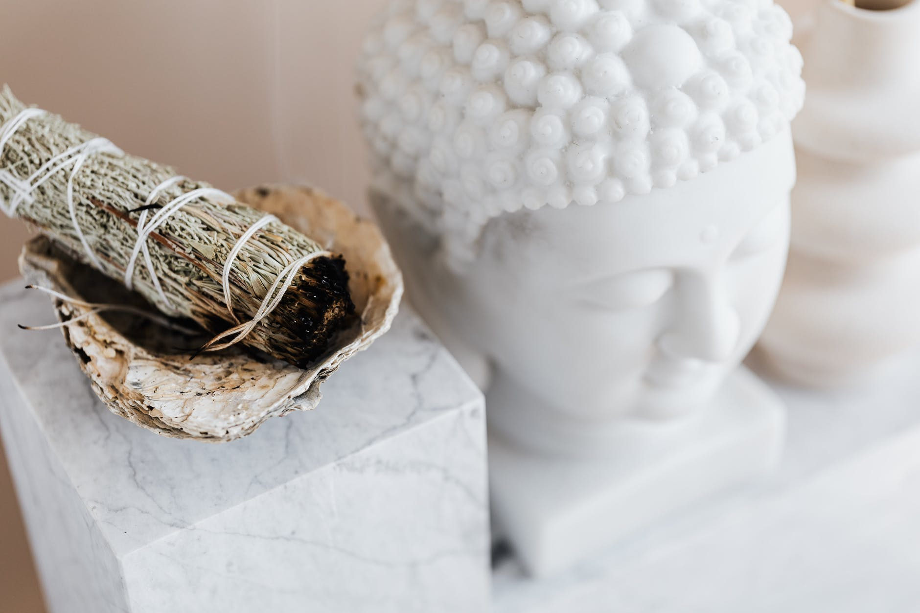 sage smudge stick in bowl on marble shelf near buddha head. figures and scents both helpful to set the tone for a meditation practice