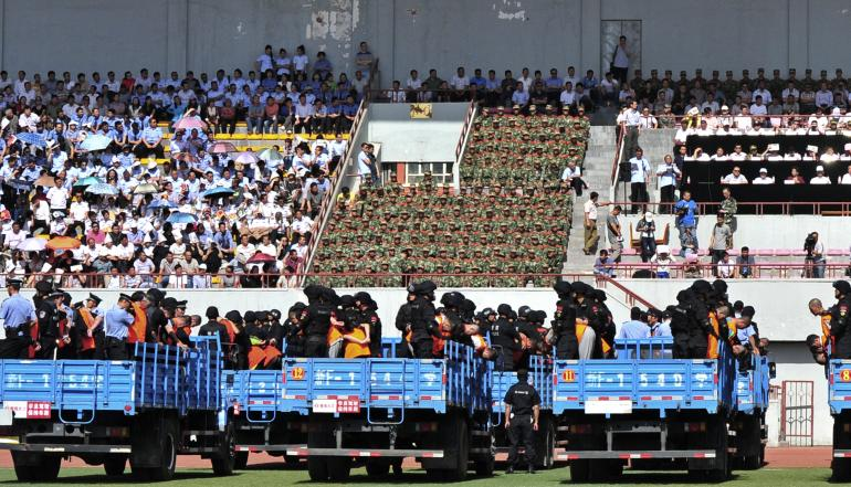 """Trucks carrying criminals and suspects are seen during a mass sentencing rally at a stadium in Yili, Xinjiang Uighur Autonomous Region on May 27, 2014. Local officials in China's western Xinjiang region held the public rally for the mass sentencing of criminals on Tuesday, handing out judgments for 55 people and at least three death sentences for crimes such as """"violent terrorism,"""" state media said. [Reuters]"""