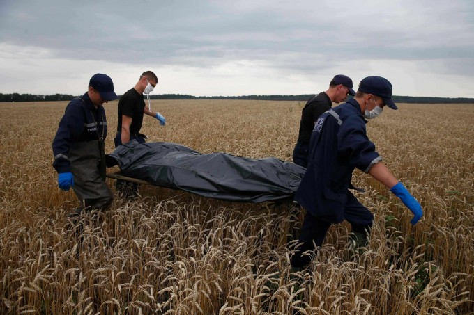 Emergency workers on Saturday carried a body from the site of the Malaysia Airlines Flight 17 crash in the Donetsk region. For many, the disaster brought home a struggle that had seemed distant. Photo: Maxim Zmeyev/Reuters